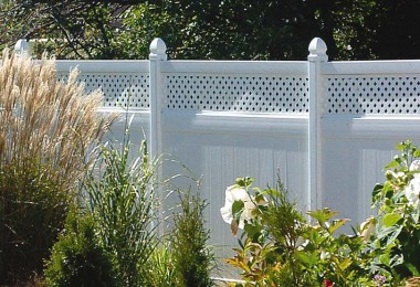 A solid privacy vinyl fence with a decorative top section creates an efficient windbreak to reduce convective heat loss from a home. Photo credit - Genova Products