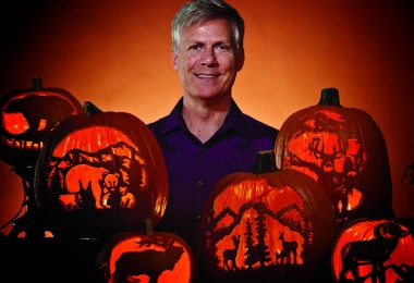 Barry Brown, master pumpkin carver, hangs out with some of his favorite jack-o'-lanterns.