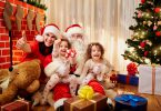 Happy family at Christmas. Mom with kids and Santa Claus