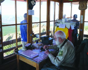 Bill Ellis works at Devil's Head Lookout as visitors enjoy the 360-degree view.
