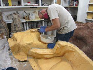 Caleb Lewis makes repairs on a Brachiosaurus mold.