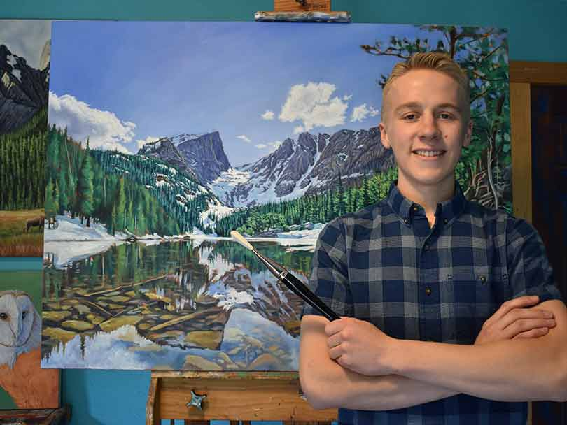 "Cody Oldham stands in front of ""Arrowhead,"" a 36-inch-by-48-inch painting of Hallett Peak."