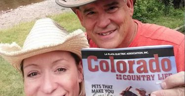 a couple smiling with their magazine at the Conejos River