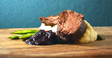 closeup of sous vide steak with blueberry sauce and asparagus