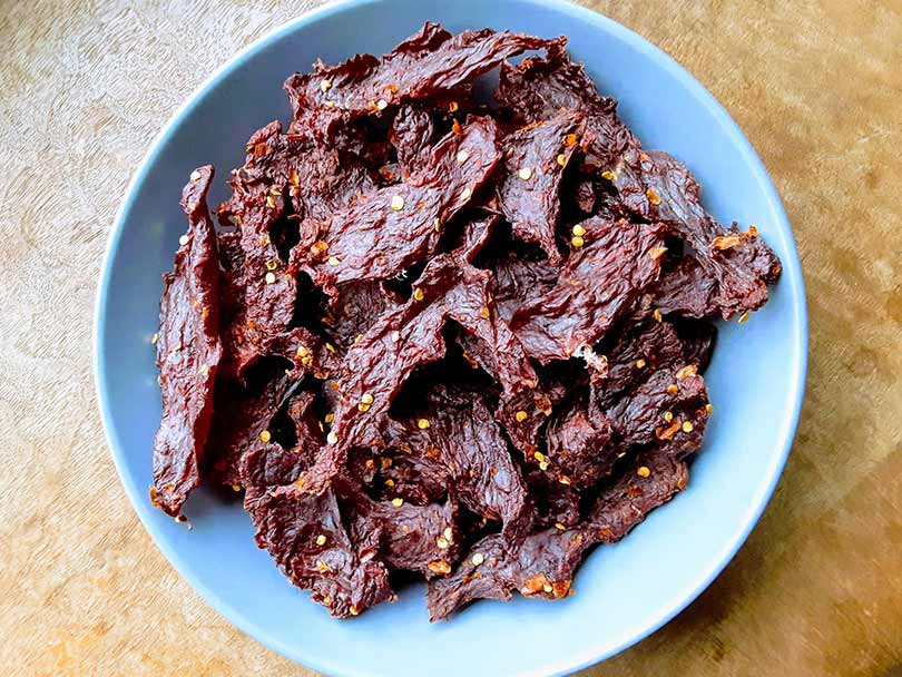 closeup of venison jerky in blue bowl