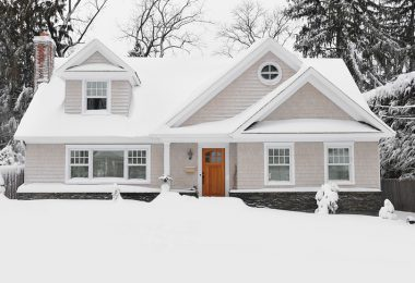 a beige, two-story home surrounded by snow