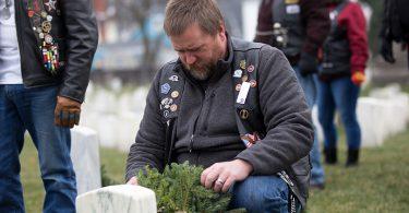 man placing Christmas wreath on grave