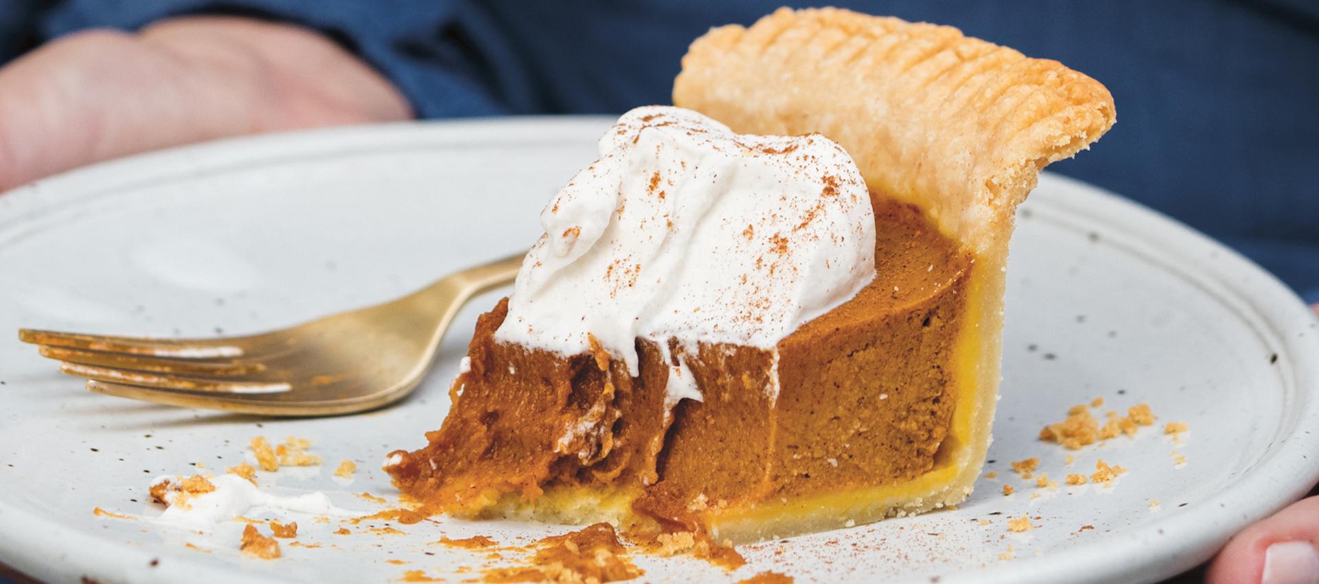 closeup of slice of half-eaten pumpkin pie