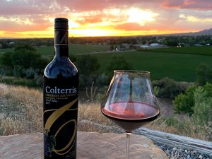 A bottle and glass of Colterris cabernet wine with the vineyard in the background