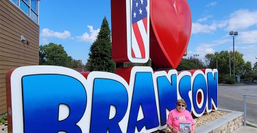 "Contest winner showing her magazine in front of an ""I Love Branson"" sign"