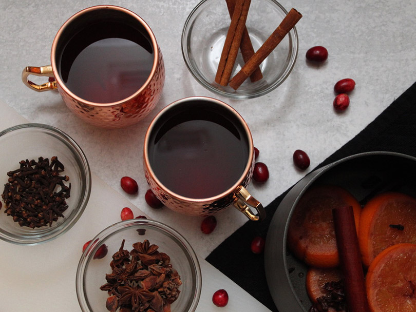 Two mugs of spice mulled wine mocktail surrounded by ingredients