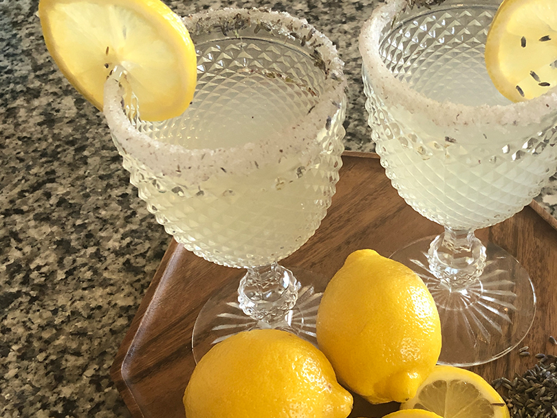 Two glasses of lavender lemon cooler with sugared rims and lemon slices